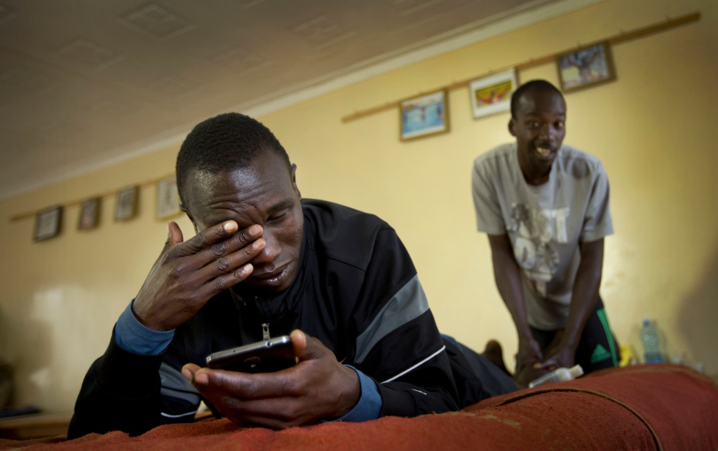 In this Jan. 30, 2016, photo Kenyan long-distance runner Geoffrey Kipsang Kamworor checks messages on his phone as he receives an after-training massage at the Global Sports camp near the village of Kaptagat in western Kenya. At the high-altitude training camp in Kenya, star athletes turn their back on modernity and bling for a simple life of hard training and communal, egalitarian living. (AP Photo/Ben Curtis)