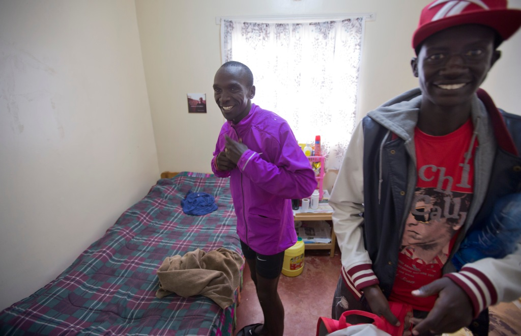 In this Jan. 30, 2016, photo winner of the London, Berlin and Chicago marathons Eliud Kipchoge, left, prepares to change clothes after his morning training run, in the small bedroom he shares with fellow runner Tareq Mubarak Taher, right, who represents Bahrain, at the Global Sports camp near the village of Kaptagat in western Kenya. At the high-altitude training camp in Kenya, star athletes turn their back on modernity and bling for a simple life of hard training and communal, egalitarian living. (AP Photo/Ben Curtis)
