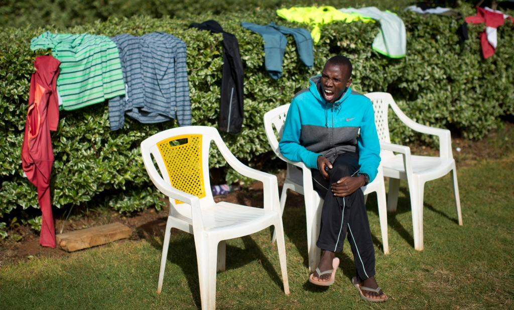 In this Jan. 30, 2016, photo sweat-soaked clothes are draped over bushes to dry in the sun, as runner Nicholas Rotich takes a rest after the morning training run, at the Global Sports camp near the village of Kaptagat in western Kenya. At the high-altitude training camp in Kenya, star athletes turn their back on modernity and bling for a simple life of hard training and communal, egalitarian living. (AP Photo/Ben Curtis)