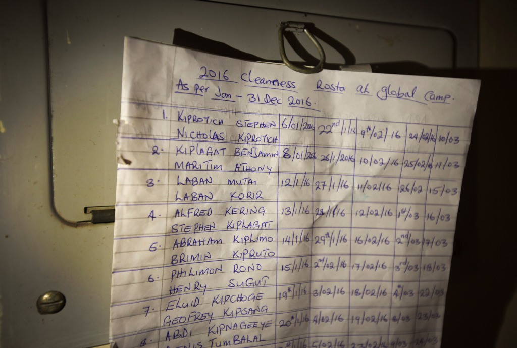 In this Jan. 30, 2016, photo a hand-written roster pinned to the wall tells runners when it's their turn to do communal chores, at the Global Sports camp near the village of Kaptagat in western Kenya. At the high-altitude training camp in Kenya, star athletes turn their back on modernity and bling for a simple life of hard training and communal, egalitarian living. (AP Photo/Ben Curtis)