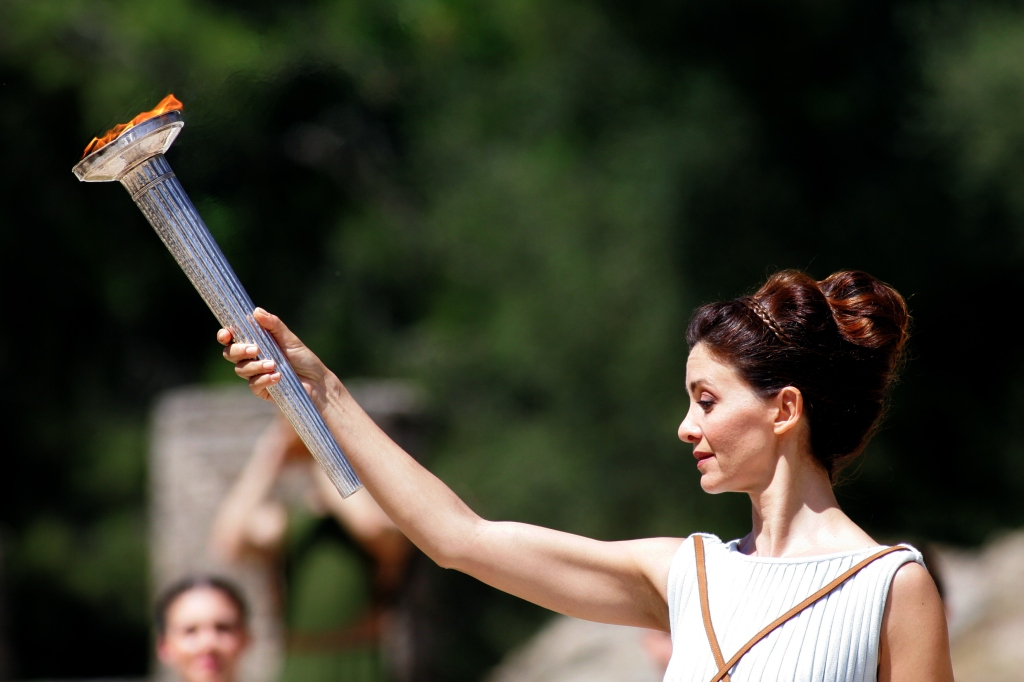 ANCIENT OLYMPIA, GREECE - 20 APRIL:Katerina Lehou, who plays the role of high priestess lights the olympic torch at the Ancient Olympia site during a rehearsal for the Lighting Ceremony of the Olympic Flame for the Rio 2o16 Olympic Games Olympic Games on April 2o in Olympia, Greece. The torch was lit using the rays of the sun in the ancient sanctuary where the Olympic Games were started in 776 BC, near the temple of Hera. (Photo by Milos Bicanski/Getty Images) *** Local Caption***