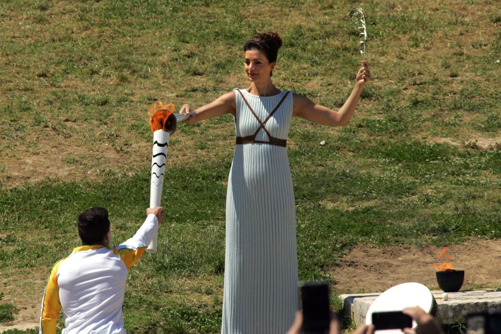 OLYMPIA, GREECE - 21 APRIL: Actress Katerina Lehou who plays the role of high priestess passes the olympic flame to the first torchbearer and reigning world champion gymnast Lefteris Petrounias during the Lighting Ceremony of the Olympic Flame for the Rio Olympic Games on April 21, 2016 in Olympia, Greece. Torchbearers will carry the Olympic Flame from Ancient Olympia on relay through Greece for eight days before a hand-over ceremony at Panathenian Stadium in Athens. (Photo by Milos Bicanski/Getty Images)