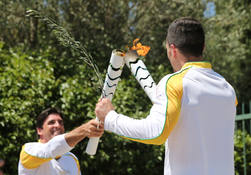 Former Brazilian volleyball player Giovane Gavio, left, receives the Olympic flame by Greek gymnast Eleftherios Petrounias, right, after the ceremonial lighting of the Olympic flame in Ancient Olympia, Greece, Thursday, April 21, 2016. The flame will be transported by torch relay to the Brazilian city of Rio de Janeiro, which will host the 2016 Olympic Games. (AP Photo/Petros Giannakouris)
