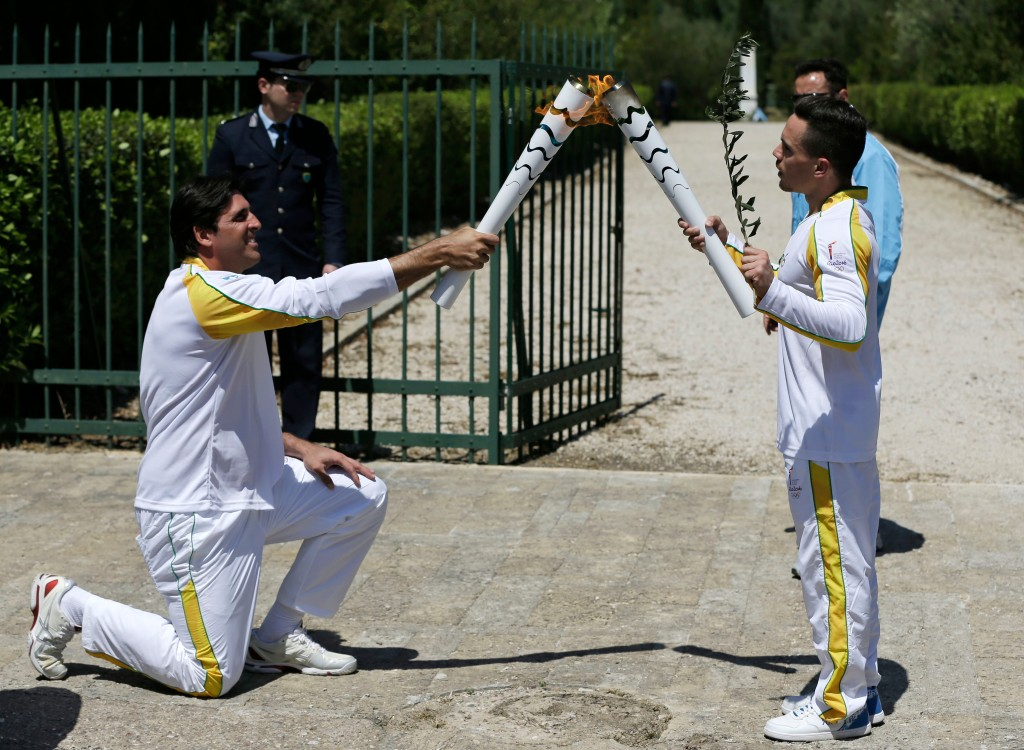Former Brazilian volleyball player Giovane Gavio, left, receivesthe Olympic flame by Greek gymnast Eleftherios Petrounias, right, after the ceremonial lighting of the Olympic flame in Ancient Olympia, Greece, Thursday, April 21, 2016. The flame will be transported by torch relay to the Brazilian city of Rio de Janeiro, which will host the 2016 Olympic Games. (AP Photo/Thanassis Stavrakis)