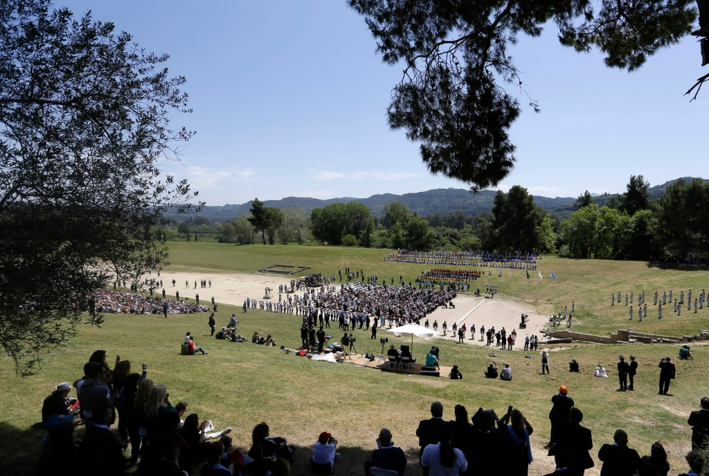 Spectators watch the ceremonial lighting of the Olympic flame in Ancient Olympia, Greece, Thursday, April 21, 2016. The flame will be transported by torch relay to the Brazilian city of Rio de Janeiro, which will host the 2016 Olympic Games. (AP Photo/Thanassis Stavrakis)