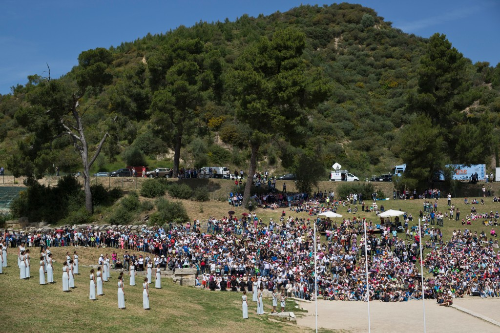Spectators watch the dress rehearsal for the lighting of the Rio de Janeiro Olympics flame, in Ancient Olympia, southern Greece, on Wednesday, April 20, 2016. The meticulously choreographed ceremony will be repeated Thursday in the ruined birthplace of the ancient Olympics in southern Greece, in the presence of top International Olympic Committee and Rio organizing officials. That will touch off a relay that will conclude with the Rio Games opening ceremony in August. (AP Photo/Petros Giannakouris)