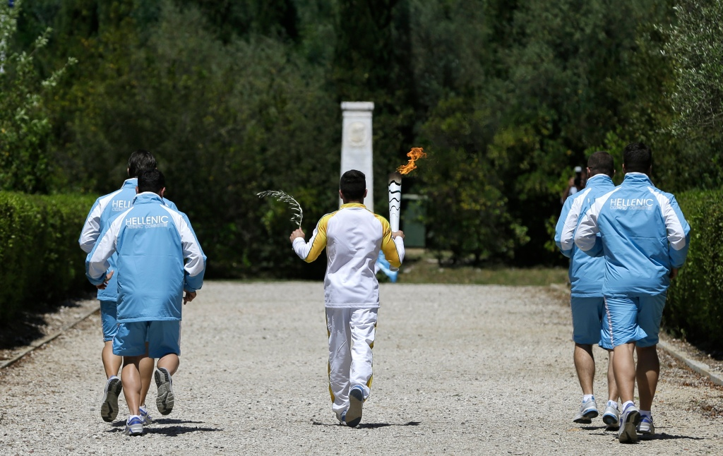 Greek gymnast Eleftherios Petrounias carries a torch with the Olympic flame during the ceremonial lighting of the Olympic flame in Ancient Olympia, Greece, Thursday, April 21, 2016. The flame will be transported by torch relay to the Brazilian city of Rio de Janeiro, which will host the 2016 Olympic Games. (AP Photo/Thanassis Stavrakis)