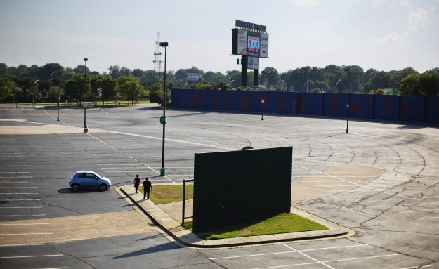 In this Wednesday, July 20, 2016 photo, visitors stand next a piece of the outfield wall of what used to be Atlanta-Fulton County Stadium, home of the 1996 Summer Olympic Games baseball event, and former home of the Atlanta Braves baseball team in Atlanta. The stadium served out the 1996 baseball season, then was imploded the following summer to make way for a parking lot serving adjacent Turner Field. (AP Photo/David Goldman)