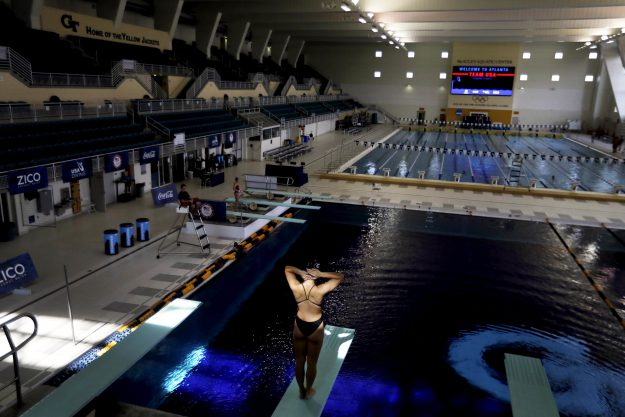 In this Friday, July 22, 2016 photo, a diver stands on a diving board during practice at Georgia Tech's McAuley Aquatic Center, home of the 1996 Summer Olympic Games swimming, diving, and synchronized swimming events in Atlanta. Temporary seating was used during the Olympics, providing a 14,600-seat main pool for swimming, diving and synchronized swimming. There also was a 4,000-seat temporary pool for water polo. After the games, Georgia Tech enclosed the facility and reduced capacity to just under 2,000. This year, it hosted the NCAA swimming championships as well as a pre-Olympic camp for the U.S. swim team before it departed for the Rio Olympics. (AP Photo/David Goldman)