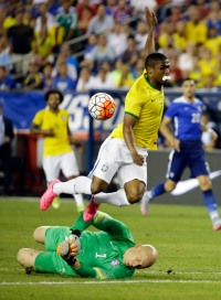 U.S. goalkeeper Brad Guzan, below, stops an attempt on goal by Brazil's Douglas Costa during the first half of an international friendly soccer match Tuesday, Sept. 8, 2015, in Foxborough, Mass. (AP Photo/Stephan Savoia)