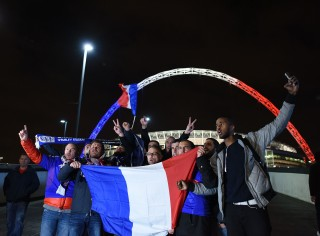 LONDON, ENGLAND - NOVEMBER 17: French fans pose for photos holding a french flag with the Wembley arch lit up in french colours in the background as they arrive ahead of tonight's International friendly match between England and France on November 17, 2015 in London, England. Security in London has tightened after a series of terror attacks across the French capital of Paris on Friday, leaving at least 129 people dead and hundreds more injured. (Photo by Ben Pruchnie/Getty Images)