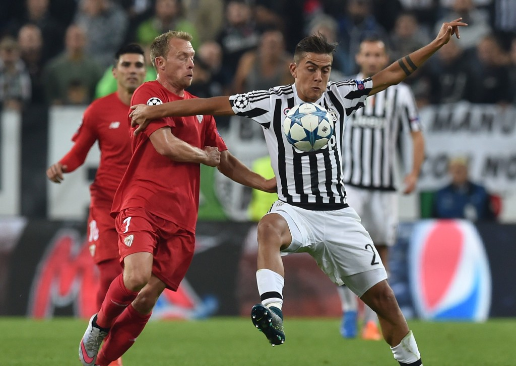 TURIN, ITALY - SEPTEMBER 30: Paulo Dybala (R) of Juventus is challenged by Michael Krohn-Dehli of Sevilla during the UEFA Champions League group E match between Juventus and Sevilla FC on September 30, 2015 in Turin, Italy. (Photo by Valerio Pennicino/Getty Images)