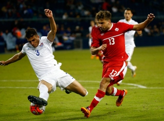 KANSAS CITY, KS - OCTOBER 01: Michael Petrasso #13 of Canada and Matt Miazga #3 of the USA compete for the ball during the 2015 CONCACAF Olympic Qualifying match at Sporting Park on October 1, 2015 in Kansas City, Kansas. (Photo by Jamie Squire/Getty Images)