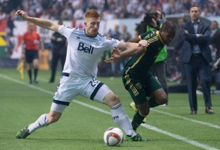 Vancouver Whitecaps FC Tim Parker (26) fights for control of the ball with Darlington Nagbe (6) of the Portland Timbers during the second half of MLS soccer action in Vancouver, British Columbia, Sunday, Nov. 8, 2015. (Jonathan Hayward/The Canadian Press via AP)
