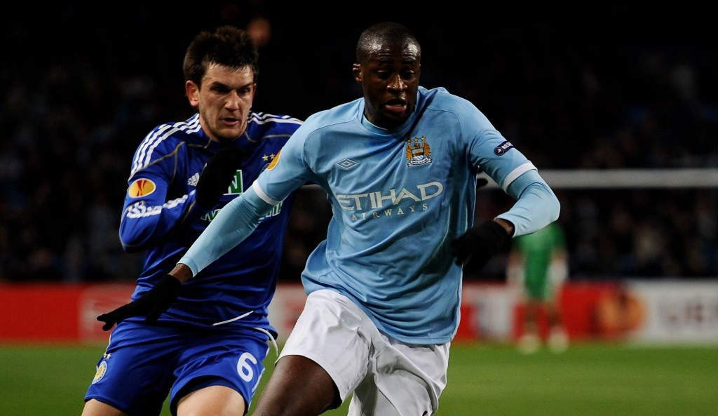 MANCHESTER, ENGLAND - MARCH 17: Yaya Toure of Manchester City holds off a challenge from Goran Popov of Dynamo Kiev during the UEFA Europa League round of 16 second leg match between Manchester City and Dynamo Kiev at City of Manchester Stadium on March 17, 2011 in Manchester, England. (Photo by Laurence Griffiths/Getty Images)