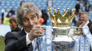 Manchester City's manager Manuel Pellegrini poses for photographers with the trophy after the English Premier League soccer match between Manchester City and West Ham at the Etihad Stadium in Manchester, England, Sunday May 11, 2014.  Manchester City won the Premier League for the second time in three seasons on Sunday, completing its campaign with a comfortable 2-0 victory over West Ham that lacked any of the drama of its previous title.  (AP Photo/Jon Super)