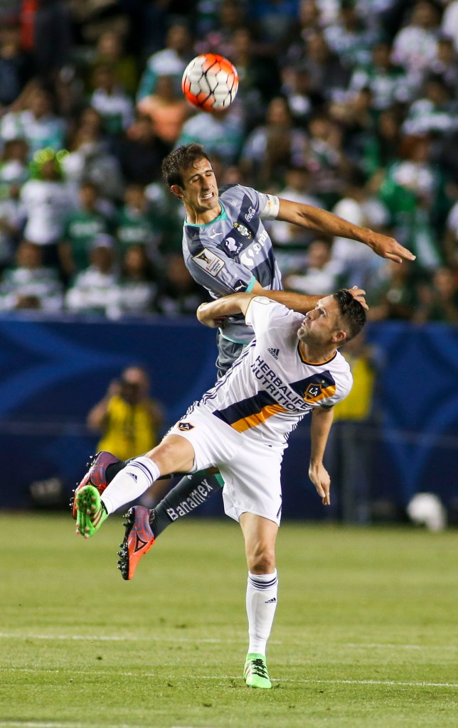 Santos Laguna's Jose Abella goes for a head ball over Los Angeles Galaxy's Robbie Keane during the first half of a CONCACAF Champions League soccer quarterfinal in Carson, Calif., Wednesday, Feb. 24, 2016. (AP Photo/Ringo H.W. Chiu)
