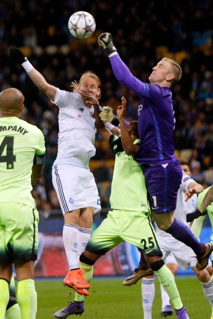 Manchester City's goalkeeper Joe Hart, right,  goes for a high ball during the Champions League round of 16 first leg soccer match between Dynamo Kiev and Manchester City at the Olympiyskiy stadium in Kiev, Ukraine, Wednesday, Feb. 24 2016.  (AP Photo/Sergei Chuzavkov)