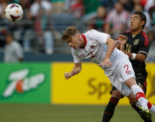 SEATTLE, WA - JULY 11: Nikolas Ledgerwood #2 of Canada heads the ball against Marco Fabian #10 of Mexico at CenturyLink Field on July 11, 2013 in Seattle, Washington. (Photo by Otto Greule Jr/Getty Images)