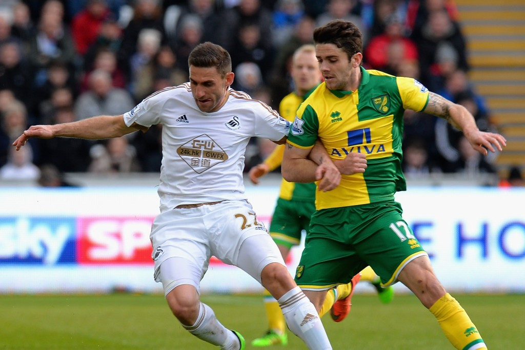 SWANSEA, WALES - MARCH 05: Angel Rangel of Swansea City is tackled by Robbie Brady of Norwich City during the Barclays Premier League match between Swansea City and Norwich City at Liberty Stadium on March 5, 2016 in Swansea, Wales. (Photo by Tony Marshall/Getty Images)