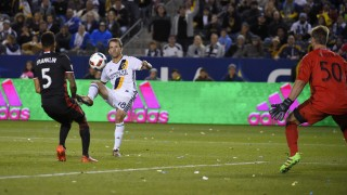 Los Angeles Galaxy forward Mike Magee, center, kicks the ball past D.C. United goalkeeper Andrew Dykstra, right, for a goal as defender Sean Franklin defends during the second half of an Major League Soccer match, Sunday, March 6, 2016, in Carson, Calif. The Galaxy won 4-1. (AP Photo/Mark J. Terrill)