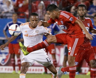 FC Dallas midfielder Victor Ulloa (8) kicks the ball in front of Houston Dynamo midfielder Ricardo Clark (13) during the second half of an MLS soccer game in Frisco, Texas, Friday, June 26, 2015. Dallas won 2-0. (AP Photo/LM Otero)