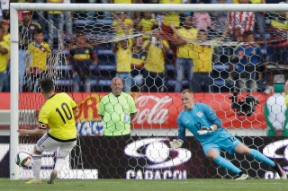 United States' goalkeeper Cody Cropper, right, fails to block Colombia's Juan Quintero from scoring from the penalty spot during a U-23 first leg soccer match qualifier for the 2016 Rio Olympics at the Roberto Melendez Stadium in Barranquilla, Colombia, Friday, March 25, 2016. (AP Photo/Fernando Vergara)