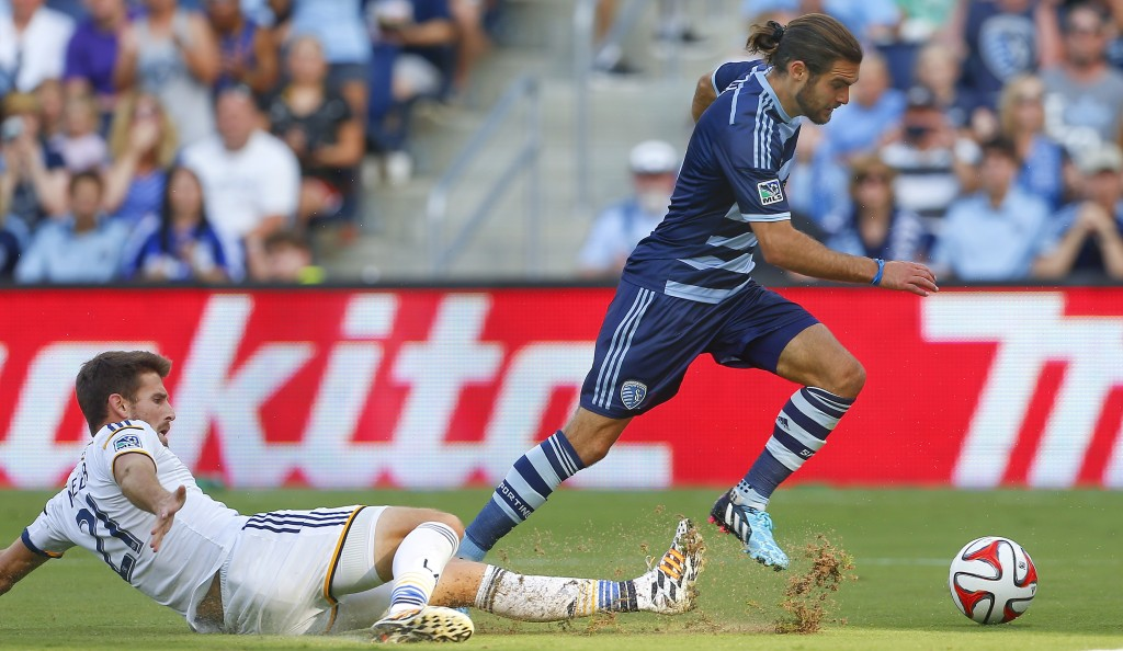 Sporting Kansas City's Graham Zusi, right, avoids a tackle by Los Angeles Galaxy's Tommy Meyer while heading toward the goal during the second half of an MLS soccer game Saturday, July 19, 2014, in Kansas City, Kan. (AP Photo/Topeka Capital-Journal, Chris Neal)