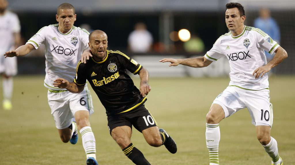 Columbus Crew forward Federico Higuain (10) battles for the ball against Seattle Sounders midfielders Osvaldo Alonso (6) and and Marco Pappa (10) during the first half of an MLS soccer game in Columbus, Ohio, on Saturday, May 9, 2015. (Kyle Robertson/Columbus Dispatch via AP)