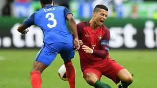 PARIS, FRANCE - JULY 10: Cristiano Ronaldo (R) of Portugal is challenged by Patrice Evra (L) of France during the UEFA EURO 2016 Final match between Portugal and France at Stade de France on July 10, 2016 in Paris, France. (Photo by Laurence Griffiths/Getty Images)