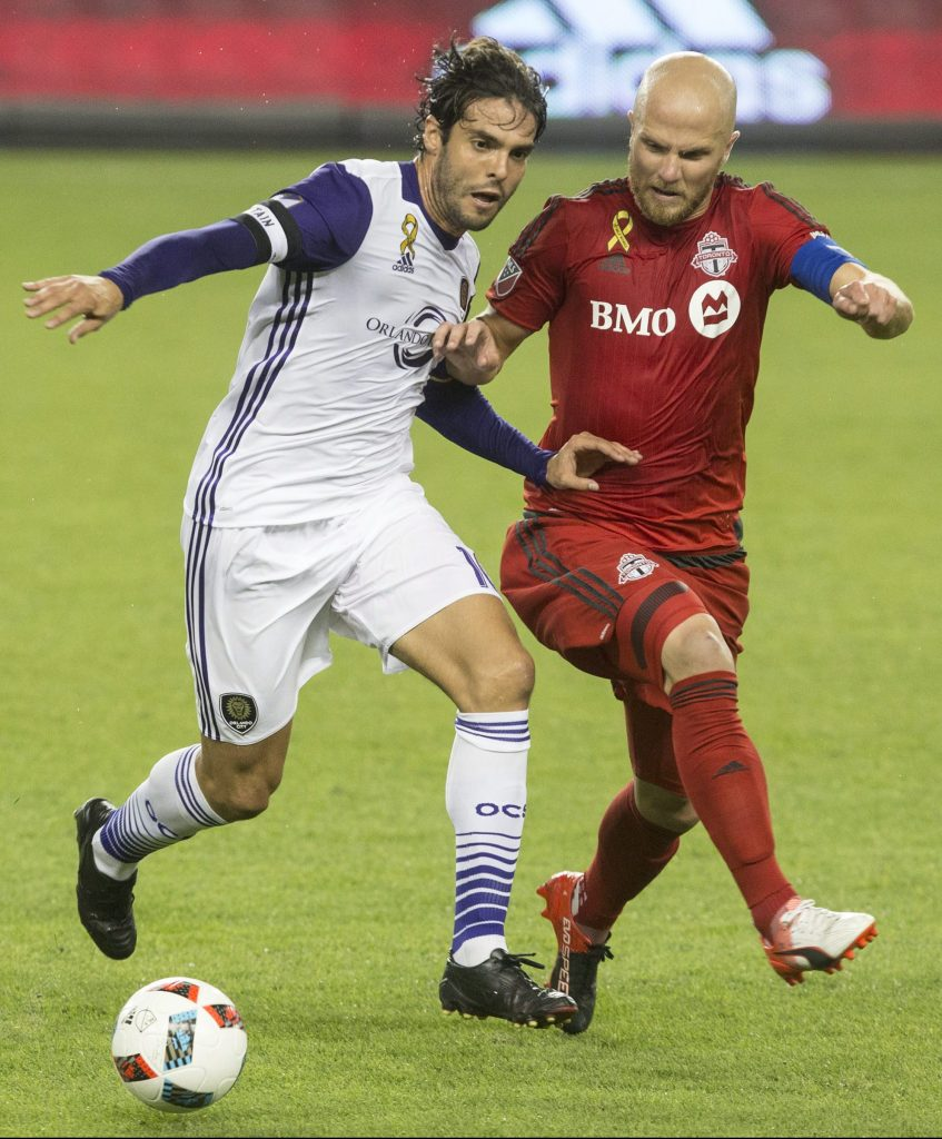 Orlando City's Kaka, center, battles with Toronto FC's Michael Bradley, right, as Amando Cooper looks on during the first half of a soccer game, Wednesday, Sept. 28, 2016 in Toronto. (Chris Young/The Canadian Press via AP)