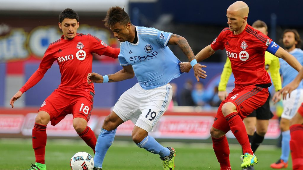 NEW YORK, NY - MARCH 13: Khiry Shelton #19 of New York City FC carries the ball against Marco Delgado #18 and Michael Bradley #4 of Toronto FC at Yankee Stadium on March 13, 2016 in the Bronx borough of New York City. (Photo by Mike Stobe/Getty Images)