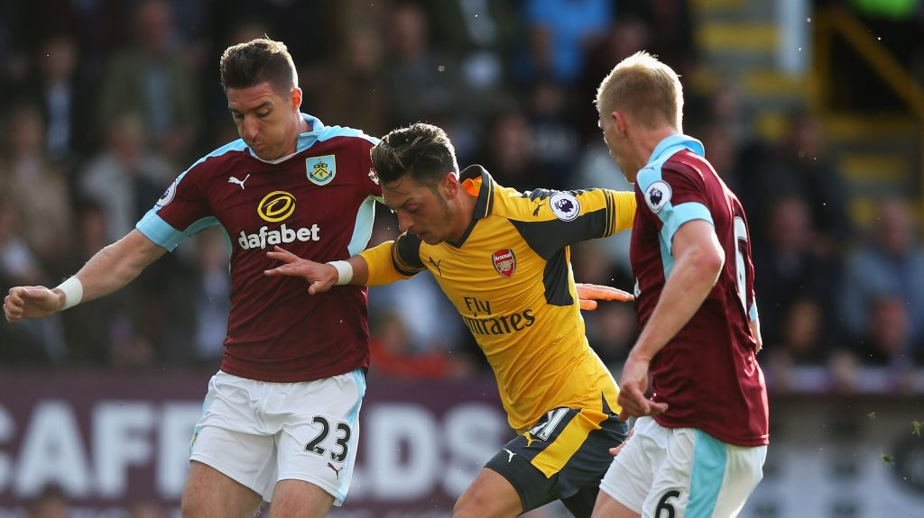 BURNLEY, ENGLAND - OCTOBER 02: Mesut Ozil of Arsenal (C) battles for possession with Burnley duo Stephen Ward of Burnley (L) and Ben Mee of Burnley (R) during the Premier League match between Burnley and Arsenal at Turf Moor on October 2, 2016 in Burnley, England. (Photo by Alex Livesey/Getty Images)