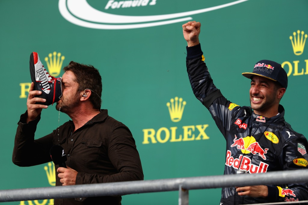 AUSTIN, TX - OCTOBER 23: Actor Gerard Butler does a shoey on the podium with Daniel Ricciardo of Australia and Red Bull Racing after Daniel finished third in the race during the United States Formula One Grand Prix at Circuit of The Americas on October 23, 2016 in Austin, United States. (Photo by Clive Mason/Getty Images)