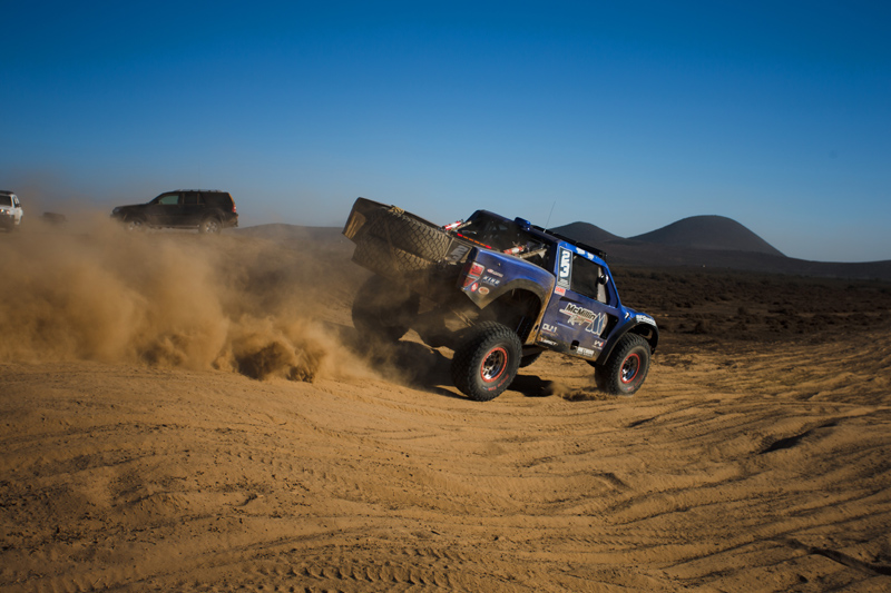 This is Baja. Flat out over rough terrain with road cars on highway as backdrop. Photo: Art Eugenio/GetSomePhoto