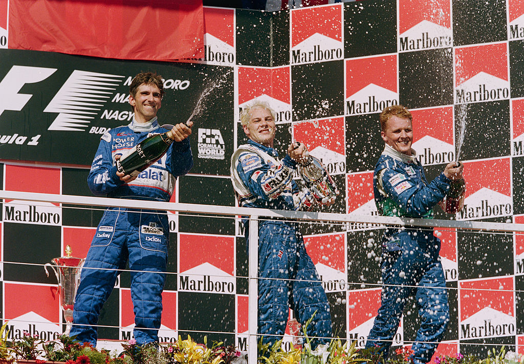 Jacques Villeneuve (C) of Canada sprays champagne to celebrate with second placed Damon Hill (L) and third placed Johnny Herbert after winning the Hungarian Grand Prix on 10th August 1997 at the Hungaroring Circuit, Budapest, Hungary. (Photo by Mark Thompson/Getty Images)