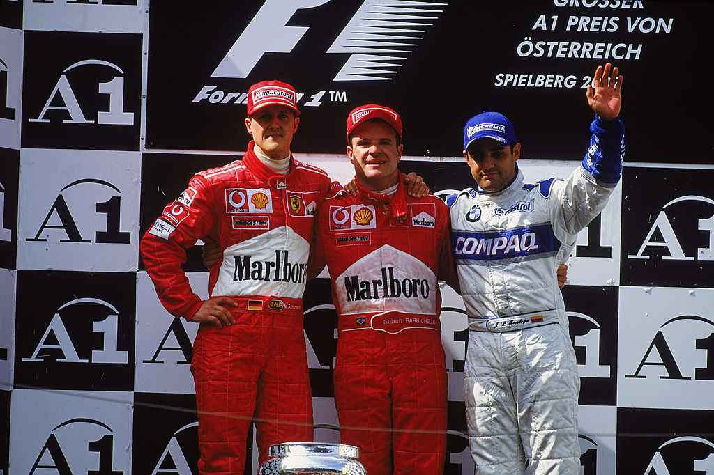 A1 RING - MAY 12: (from left to right) Race winner Ferrari driver Michael Schumacher of Germany, runner-up Ferrari driver Rubens Barrichello of Brazil and third placed BMW-Williams driver Juan Pablo Montoya of Colombia stand on the podium after the Austrian Formula One Grand Prix held at the A1 Ring in Spielberg, Austria on May 12, 2002. (Photo by Tom Shaw/Getty Images)