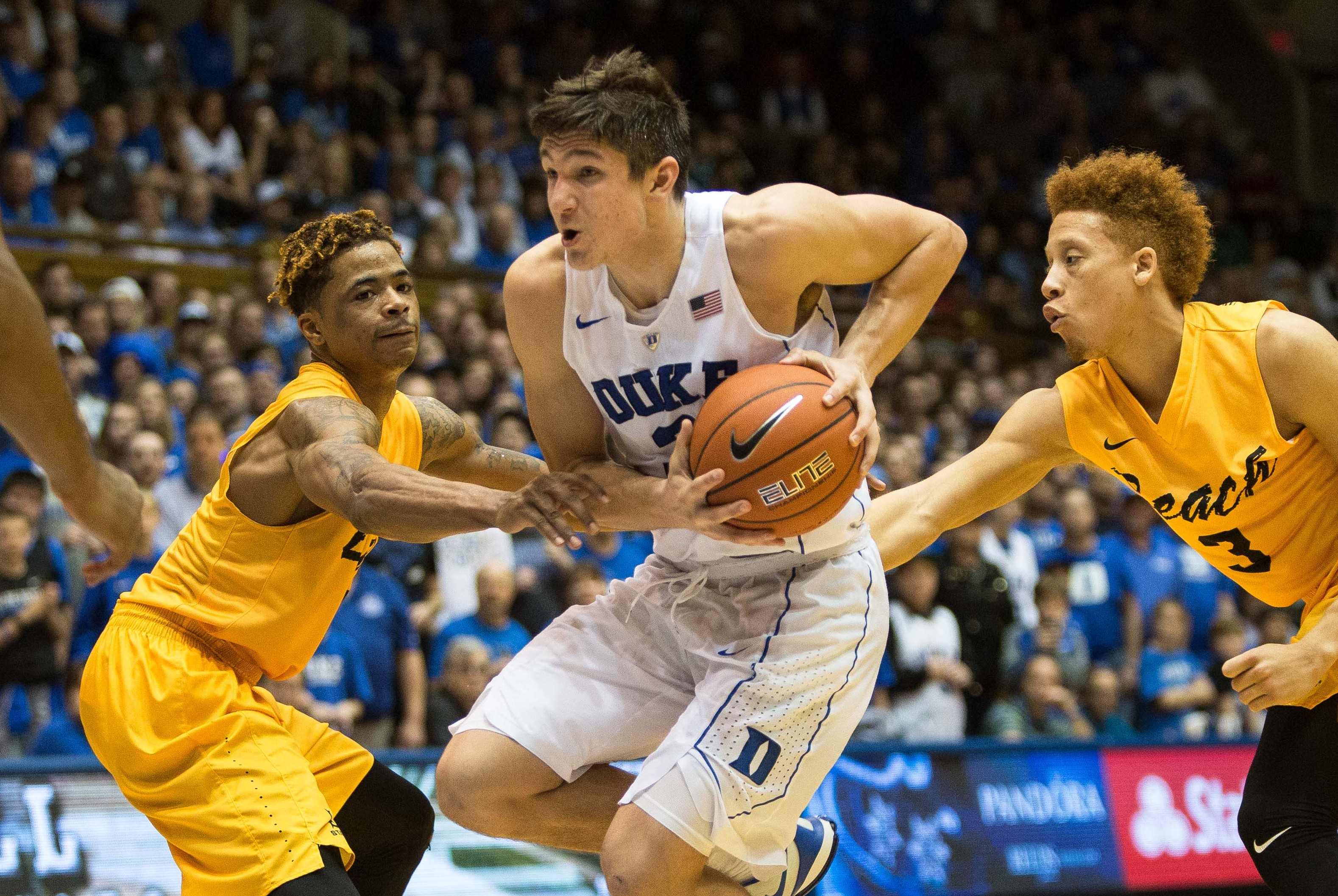 Duke's Grayson Allen, center, handles the ball as Long Beach State's Nick Faust, left, and Long Beach State's Noah Blackwell (3) defend during the second half of an NCAA college basketball game in Durham, N.C. Wednesday, Dec. 30, 2015. Duke won 103-81. (AP Photo/Ben McKeown)