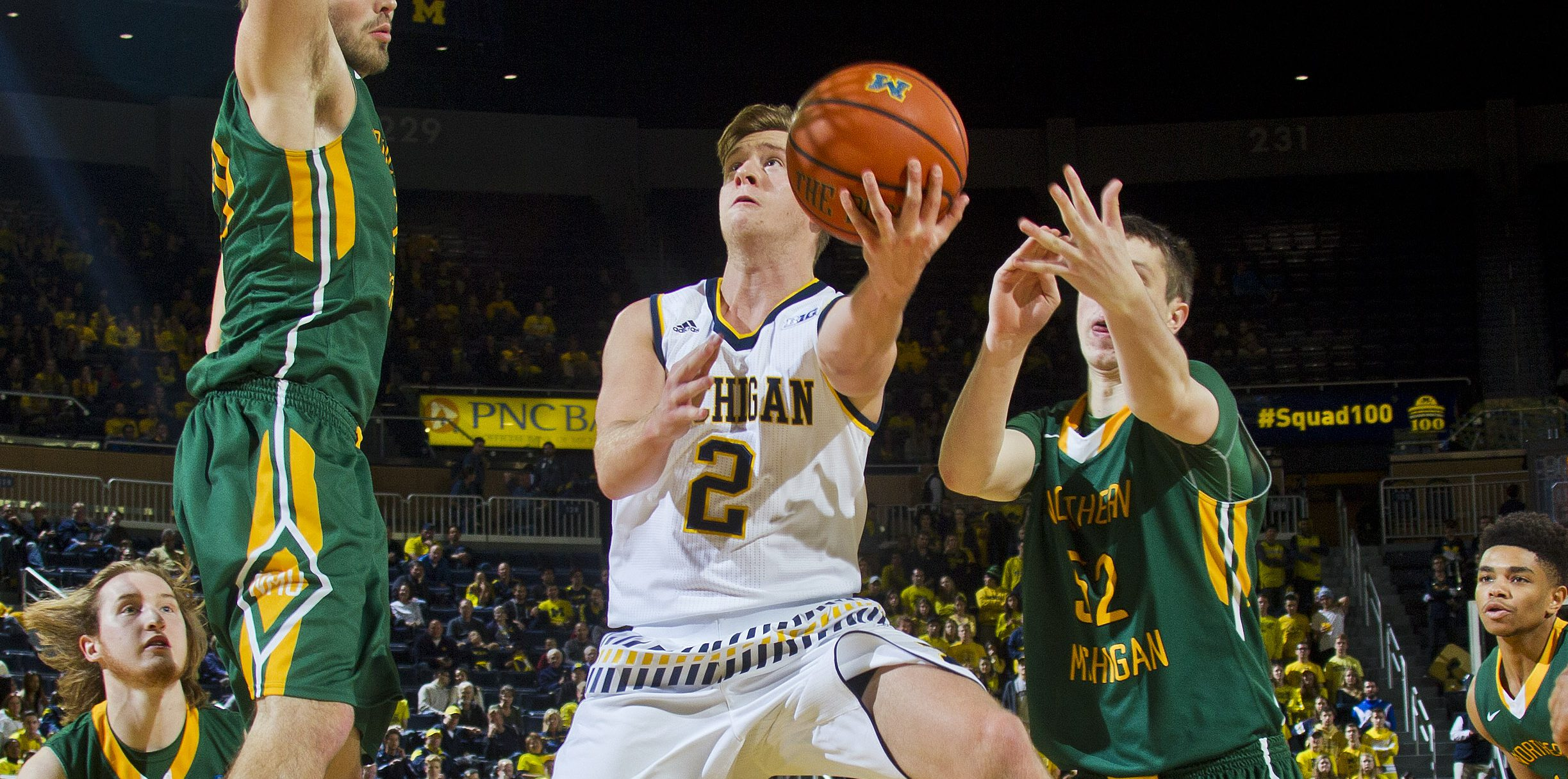 Michigan guard Spike Albrecht (2) makes a layup between Northern Michigan forward Brett Branstrom, top left, and center Vejas Grazulis (52) in the second half of an NCAA college basketball game at Crisler Center in Ann Arbor, Mich., Friday, Nov. 13, 2015. Michigan won 70-44. (AP Photo/Tony Ding)