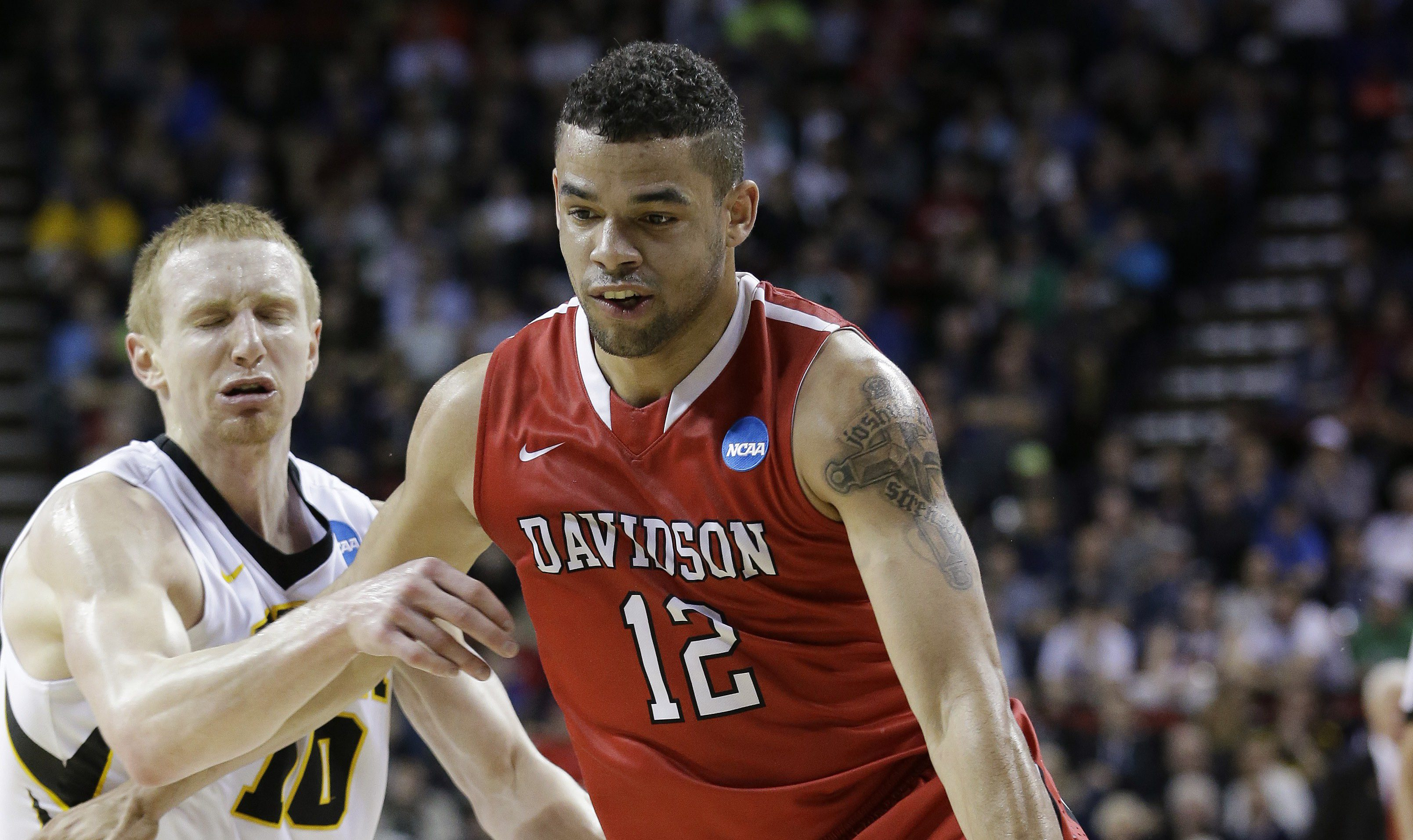 Davidson's Jack Gibbs (12) tries to drive past Iowa's Mike Gesell during the first half of an NCAA tournament college basketball game in the Round of 64 in Seattle, Friday, March 20, 2015. (AP Photo/Elaine Thompson)