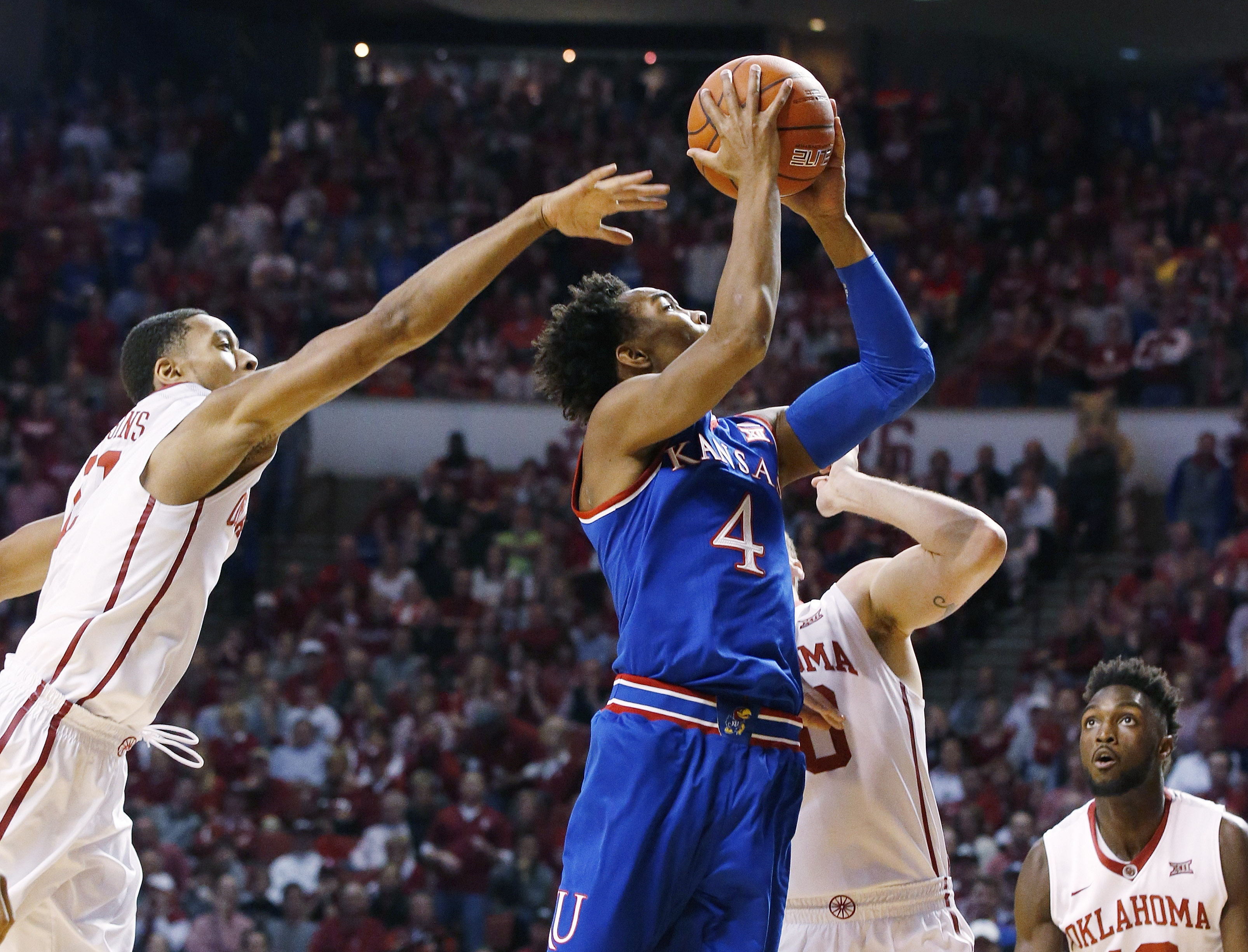 Kansas guard Devonte' Graham (4) shoots between Oklahoma guard Isaiah Cousins, left, forward Ryan Spangler, center, and forward Khadeem Lattin, right, in the first half of an NCAA college basketball game in Norman, Okla., Saturday, Feb. 13, 2016. (AP Photo/Sue Ogrocki)