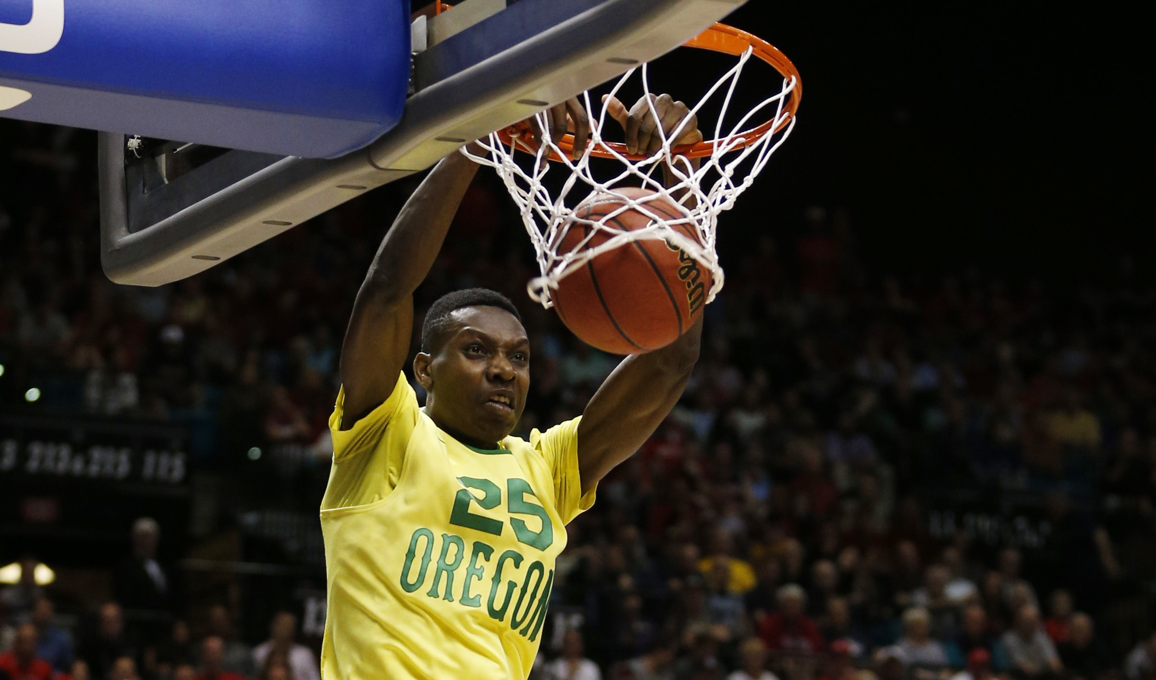 Oregon forward Chris Boucher dunks over Arizona forward Ryan Anderson (12) and center Dusan Ristic (14) during the second half of an NCAA college basketball game in the semifinals of the Pac-12 men's tournament Friday, March 11, 2016, in Las Vegas. Oregon won in overtime, 95-89. (AP Photo/John Locher)