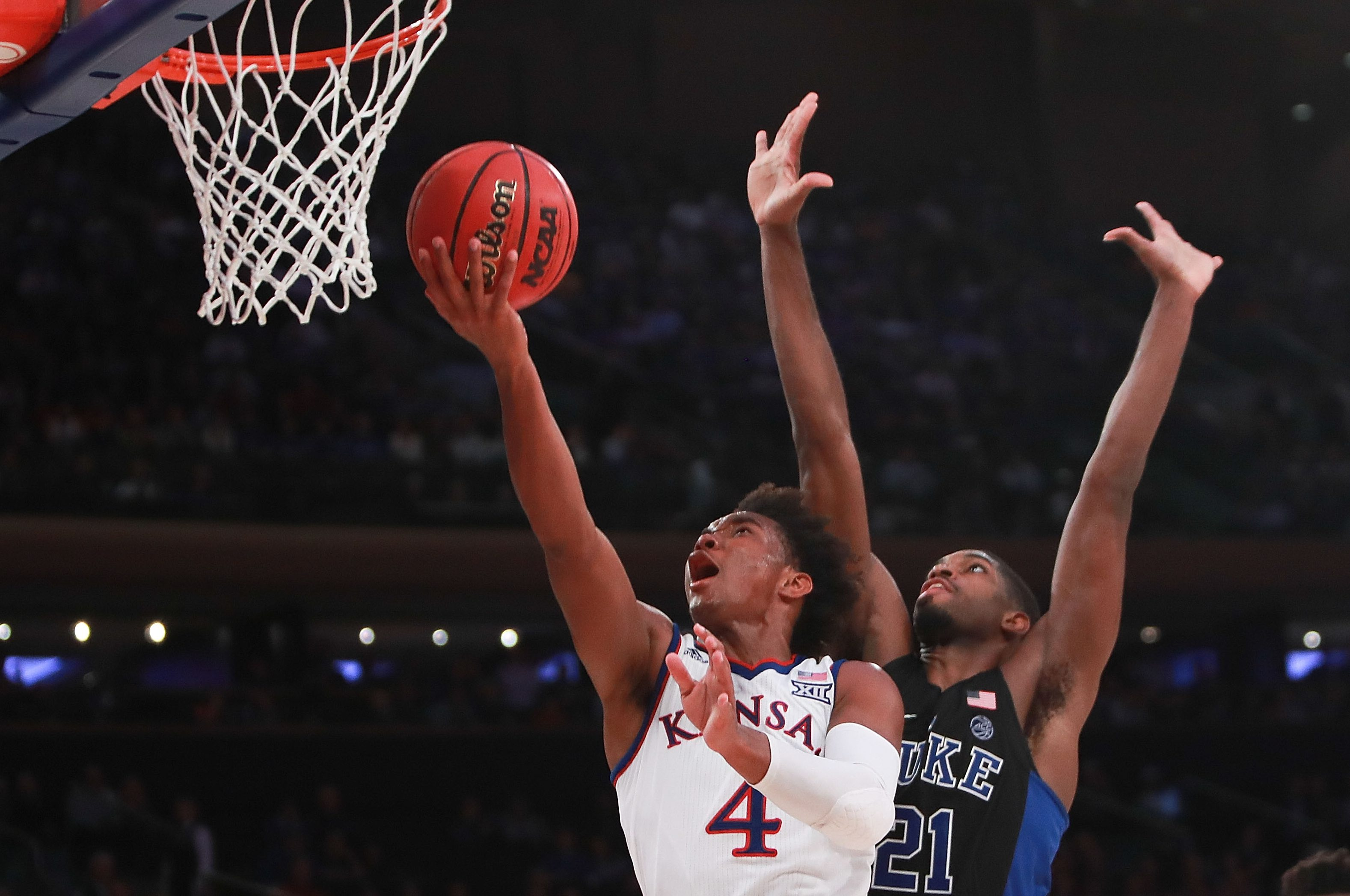 NEW YORK, NY - NOVEMBER 15: Devonte' Graham #4 of the Kansas Jayhawks puts up a layup over Amile Jefferson #21 of the Duke Blue Devils in the second half during the State Farm Champions Classic at Madison Square Garden on November 15, 2016 in New York City. (Photo by Michael Reaves/Getty Images)