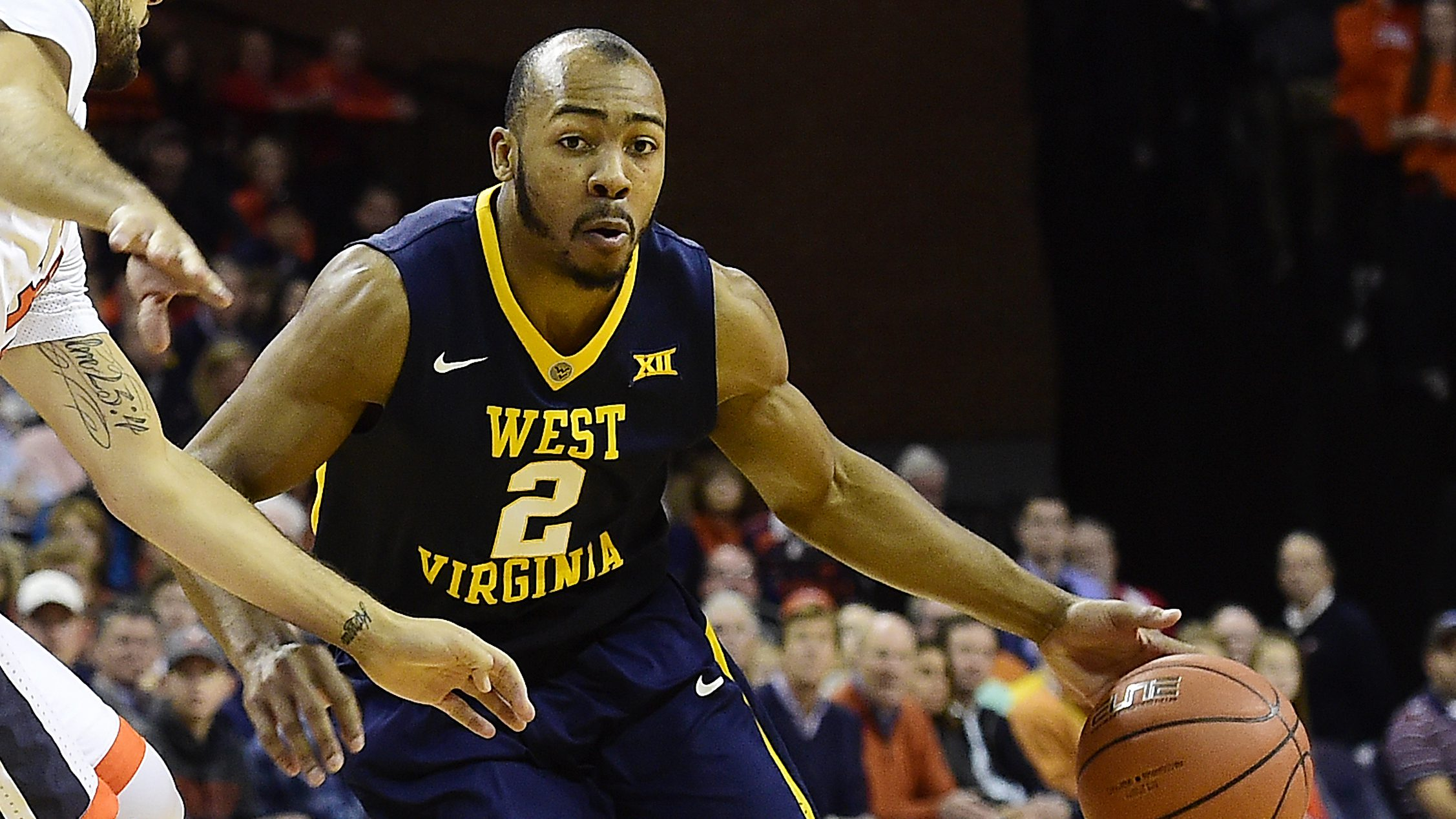 CHARLOTTESVILLE, VA - DECEMBER 03: Jevon Carter #2 of the West Virginia Mountaineers dribbles the ball against London Perrantes #32 of the Virginia Cavaliers in the first half during a game at John Paul Jones Arena on December 3, 2016 in Charlottesville, Virginia. (Photo by Patrick McDermott/Getty Images)