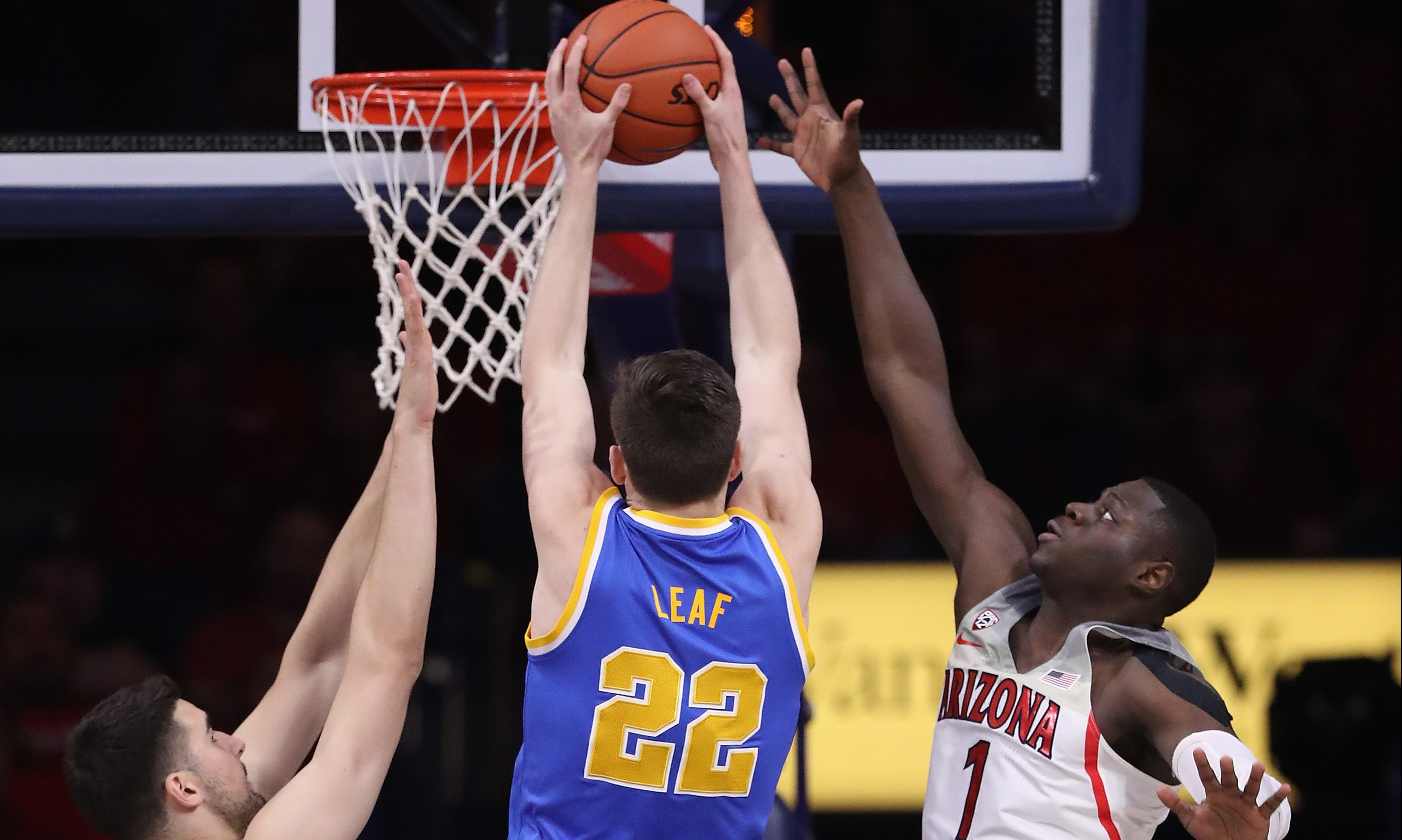 TUCSON, AZ - FEBRUARY 25:  TJ Leaf #22 of the UCLA Bruins attempts a shot between Dusan Ristic #14 and Rawle Alkins #1 of the Arizona Wildcats during the first half of the college basketball game at McKale Center on February 25, 2017 in Tucson, Arizona.  (Photo by Christian Petersen/Getty Images)