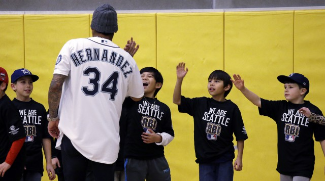 Children reach to high-five Seattle Mariners' Felix Hernandez after the pitcher participated an instructional clinic that included a game of wiffle ball at the Rainier Vista Boys & Girls Club, Monday, Nov. 16, 2015, in Seattle. Earlier at the club, Hernandez presented $100,000 in total grants to five Seattle area nonprofits as part of the Major League Baseball Players Association/Major League Baseball Joint Youth Initiative Players Going Home program. (AP Photo/Elaine Thompson)