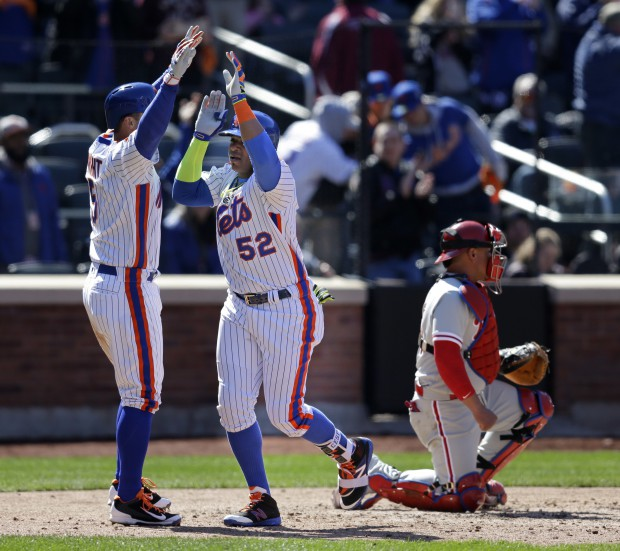 New York Mets' Yoenis Cespedes, center, is greeted by David Wright, left, after hitting a two-run home run during the sixth inning of the baseball game against the Philadelphia Phillies at Citi Field, Sunday, April 10, 2016 in New York. (AP Photo/Seth Wenig)