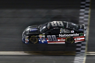 DAYTONA BEACH, FL - JULY 06: Dale Earnhardt Jr., driver of the #88 Nationwide Stars and Stripes Chevrolet, takes the checkered flag to win the NASCAR Sprint Cup Series Coke Zero 400 Powered by Coca-Cola at Daytona International Speedway on July 6, 2015 in Daytona Beach, Florida. (Photo by Patrick Smith/Getty Images)