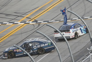 Elliott Sadler, gets out of his car and celebrates after being declared the winner of the NASCAR Xfinity Series auto race at Talladega Superspeedway, Saturday, April 30, 2016, in Talladega, Ala. NASCAR had to determine who was the actual leader when a caution froze the field in overtime. Brennan Poole (48) crossed the finish line first, but was denied his first career Xfinity Series win when NASCAR said the field was frozen with Sadler still ahead of Poole. (AP Photo/John Bazemore)