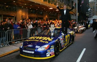NEW YORK - DECEMBER 03: 2004 NASCAR NEXTEL Cup Series Champion Kurt Busch stands on top of his car while posing with the NASCAR NEXTEL Cup trophy prior the 2004 NASCAR Nextel Cup Awards outside of the Waldorf Astoria on December 3, 2004 in New York City. (Photo by Chris Trotman/Getty Images for NASCAR)